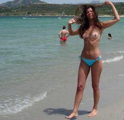 Me exibindo de topless mostrando meu corpo caminhando na praia